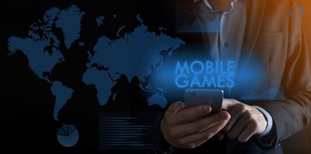 碑文の携帯ゲームでスマートフォンを持っているビジネスマン