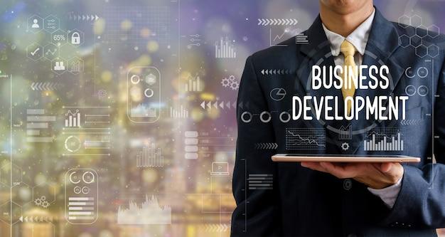 タブレットコンピュータービジネス開発アイコングラフの抽象的な背景をボケ味で保持しているビジネスマン。