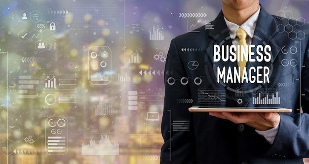 タブレットコンピュータービジネスマネージャーアイコングラフの抽象的な背景をボケ味で保持しているビジネスマン。