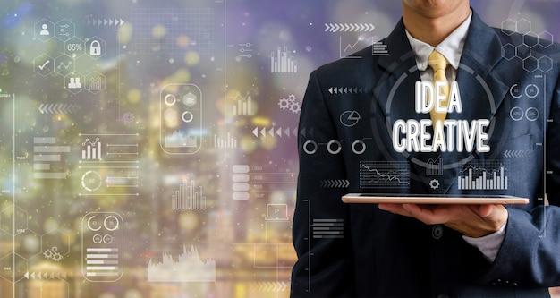 タブレットコンピューターのアイデアの創造的なアイコングラフの抽象的な背景をボケ味で保持しているビジネスマン。