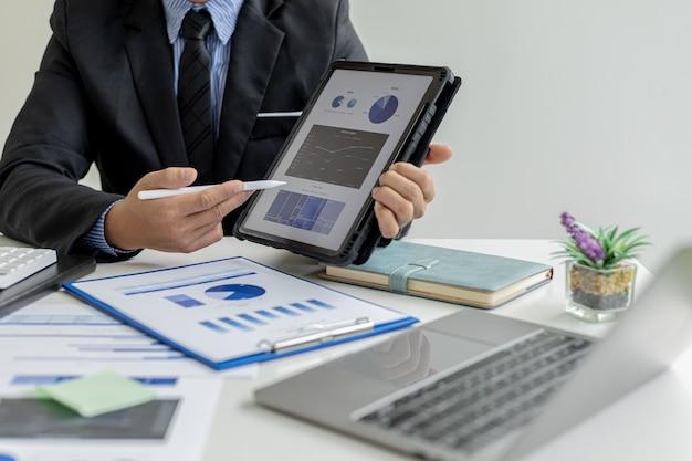 営業担当者の販売データを表示するタブレットを持っているビジネスマンは、販売マネージャーと会って販売成長管理を計画し、販売を増やすためのマーケティング計画を立てています。販売管理の概念。