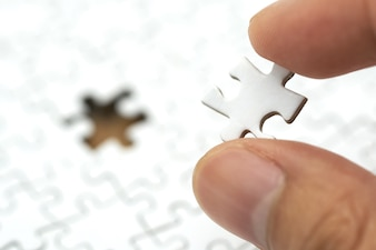 Businessman holding a white Jigsaw is placed on a white Jigsaw