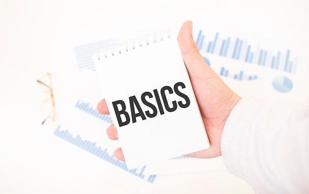 テキストbasics、ビジネスコンセプトと白いメモ帳を保持しているビジネスマン