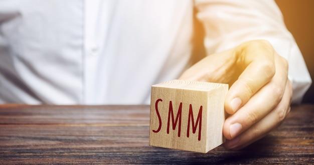 Бизнесмен, держащий деревянный блок со словом smm.