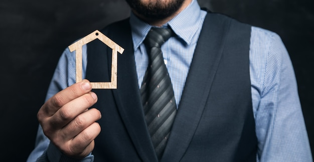 Бизнесмен, держа в руке деревянный дом на черной поверхности