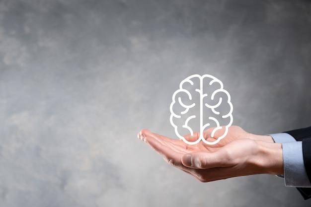 Бизнесмен, держащий абстрактный мозг и значок цифрового маркетинга, стратегии и целевой цели бизнес-инвестиций, средств массовой информации и технологий.
