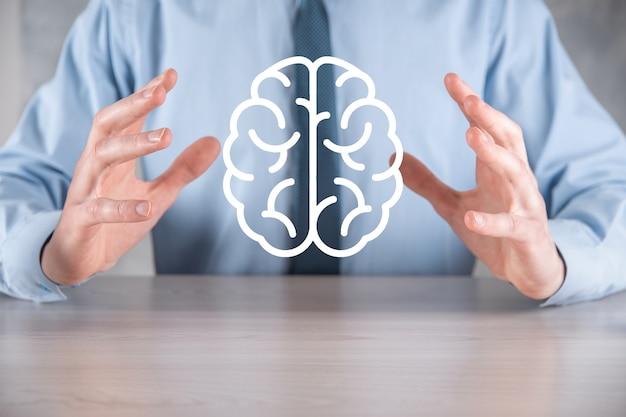 Бизнесмен, холдинг абстрактные инструменты мозга и значок