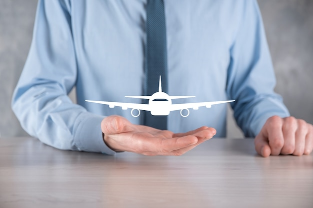 Businessman holding an airplane icon in his hands. online ticket purchase.travel.