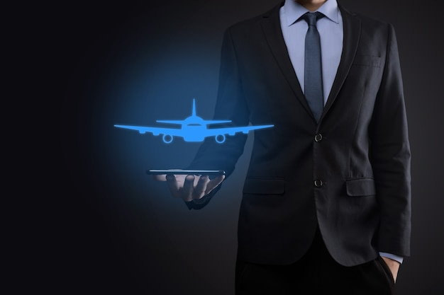 Businessman holding an airplane icon in his hands