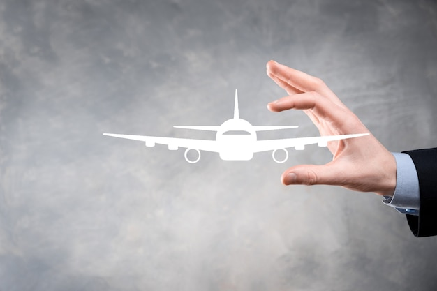 Businessman holding an airplane icon in his hands.