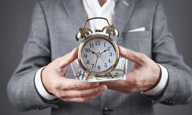 目覚まし時計とドル紙幣を保持しているビジネスマン。