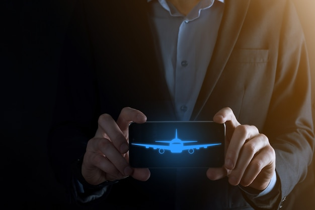 飛行機のアイコンを手に持っているビジネスマン。オンラインチケット購入。旅行。