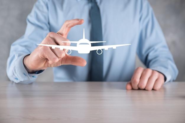 Бизнесмен, держа в руках значок самолета. покупка билетов онлайн.