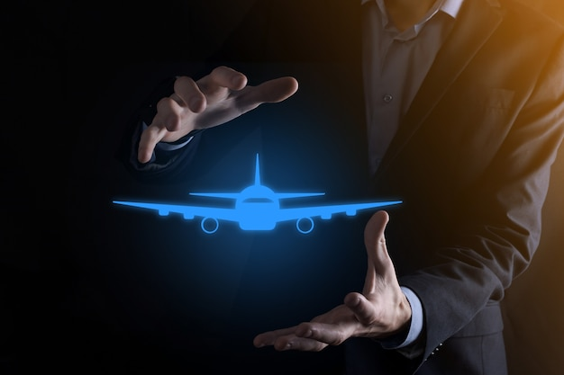 Бизнесмен, держа в руках значок самолета