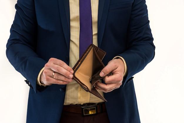 空の財布を持っているビジネスマン。絶望と失敗。惨めさ。破産または貧困の概念
