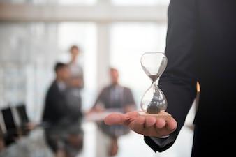 時間ガラスを持っている実業家は、時間通りになることの重要性を示しています