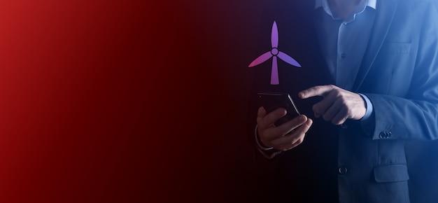 환경 에너지를 생산하는 풍차의 아이콘을 들고 사업가. 어두운 배경. 네온 레드, 블루 라이트.