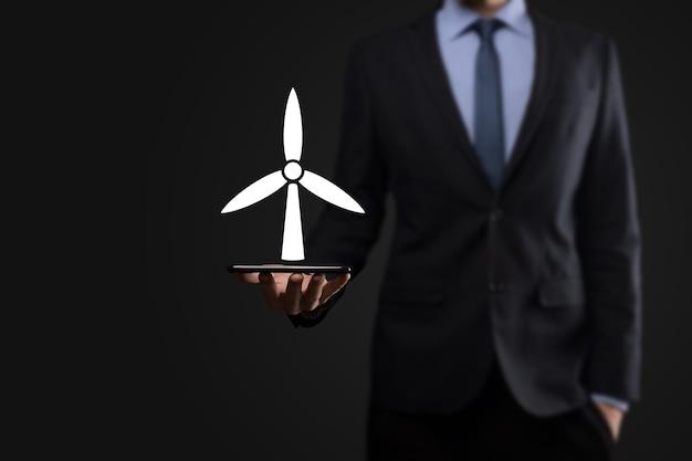 환경 에너지를 생산하는 풍차의 아이콘을 들고 사업가. 어두운 배경입니다.