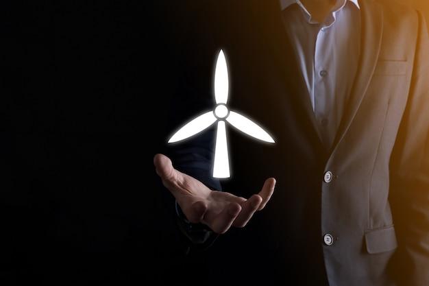 환경 에너지를 생산하는 풍차 아이콘을 들고 있는 사업가. 어두운 배경