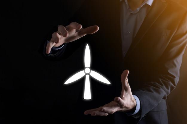 환경 에너지를 생산하는 풍차의 아이콘을 들고 사업가. 어두운 배경