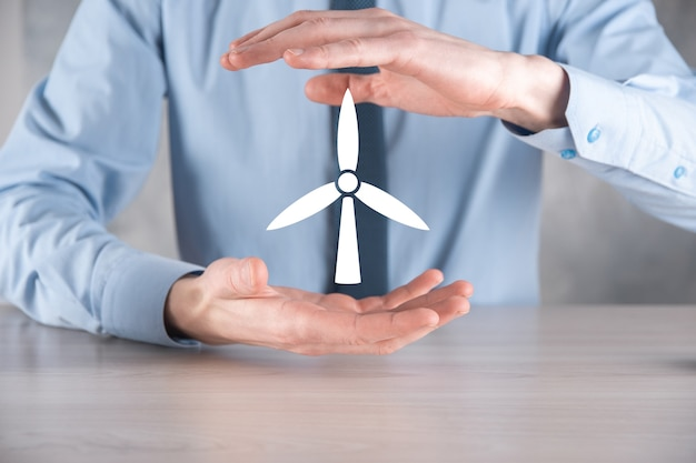 환경 에너지를 생산하는 풍차의 아이콘을 들고 사업가