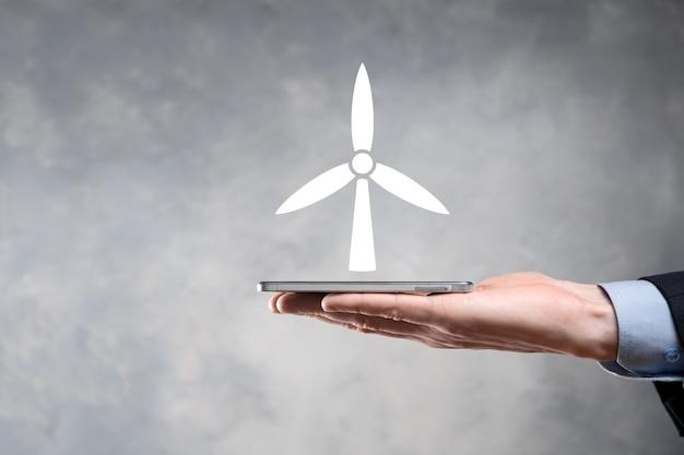 環境エネルギーを生成する風車のアイコンを保持しているビジネスマン。
