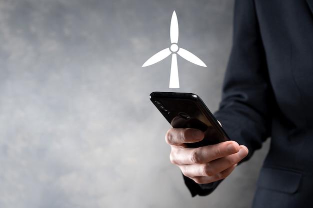 환경 에너지를 생산하는 풍차의 아이콘을 들고 사업가.
