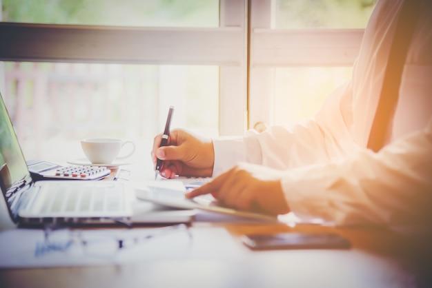 オフィスで働く投資チャートを保持し分析している実業家。ビジネスワークのコンセプト。