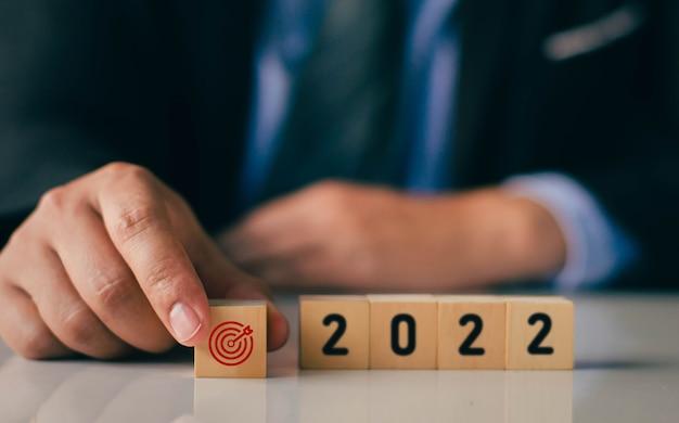Бизнесмен держит и ставит цель из деревянного блока, которая на экране печатает красную цель на деревянном кубическом блоке, начало нового года 2022 и идея новой цели с новым годом