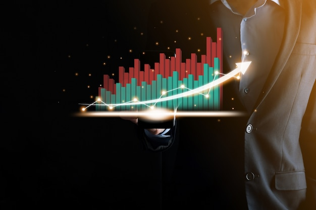 Бизнесмен, держащий и показывающий растущую виртуальную голограмму статистики, графика и диаграммы со стрелкой вверх на темном фоне. фондовый рынок. бизнес-концепция роста, планирования и стратегии.