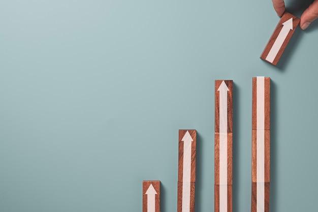 Бизнесмен держа и укладывая белую стрелку вверх, которая печатает экран на деревянном блоке на синем фоне, концепция роста прибыли бизнеса.