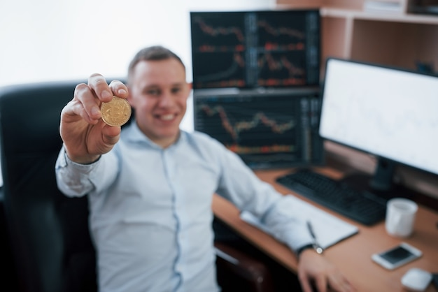 Businessman holding bitcoin in hand while sitting in modern office with many monitors with graphs.