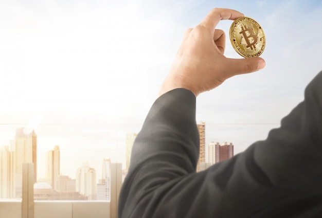 Businessman holding bitcoin on hand