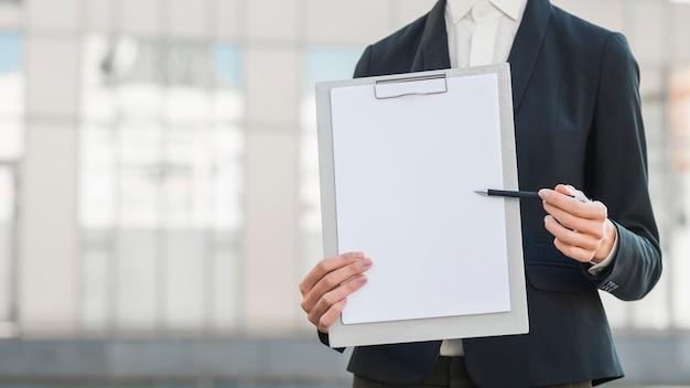 Businessman holding blank clipboard