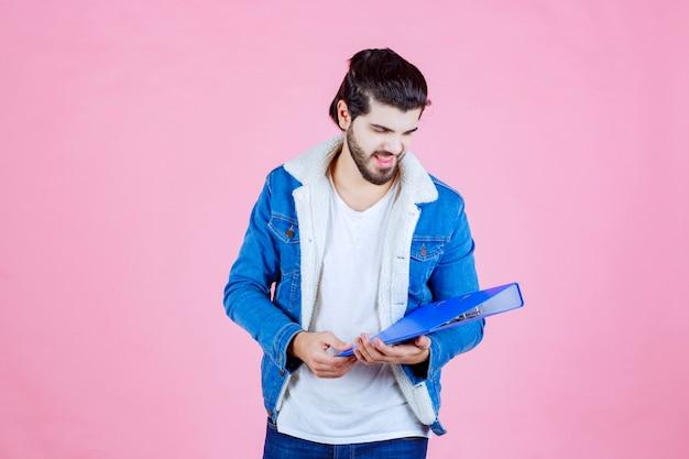 Un uomo d'affari che tiene una cartella blu e si sente soddisfatto