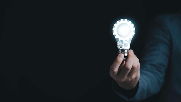 창의적인 사고 아이디어와 혁신 개념을 위해 가상 전구가 있는 파란색 기계 장비를 들고 있는 사업가입니다.
