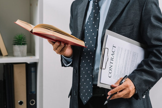 Businessman holding book and clipboard with contract