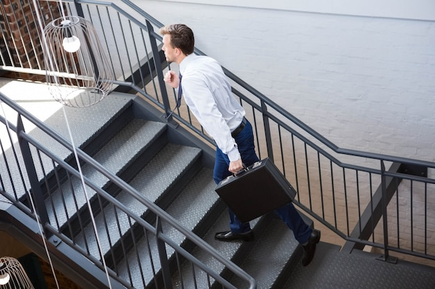 Businessman holding briefcase and climbing staircase in office