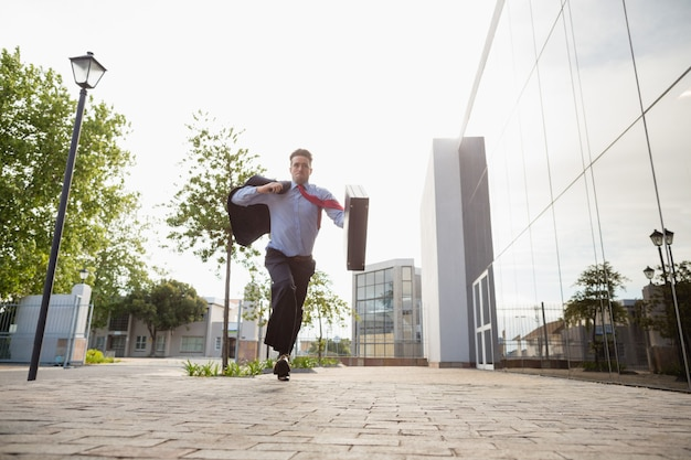 Businessman holding briefcase running