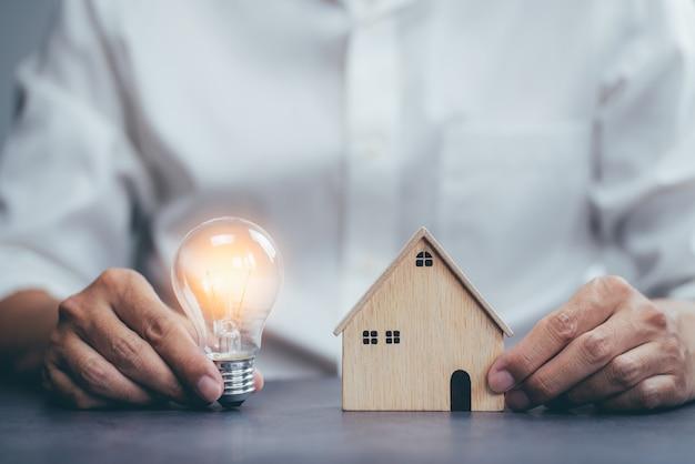明るい電球と家のモデルを保持しているビジネスマン