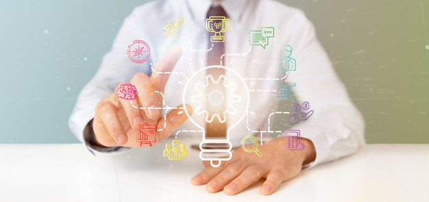 Businessman holding a bulb lamp idea  with start up icon connected