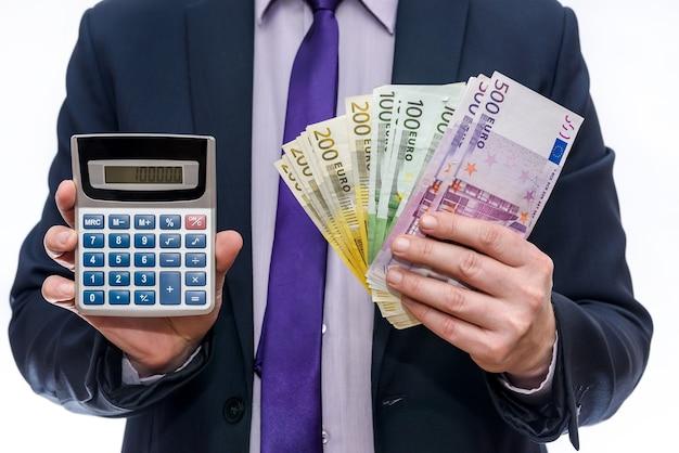 Бизнесмен, держащий калькулятор и банкноты евро крупным планом