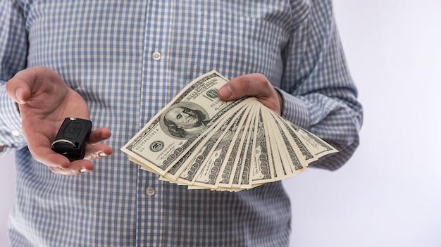 Бизнесмен держа ключ автомобиля и изолированные деньги доллара. концепция продажи