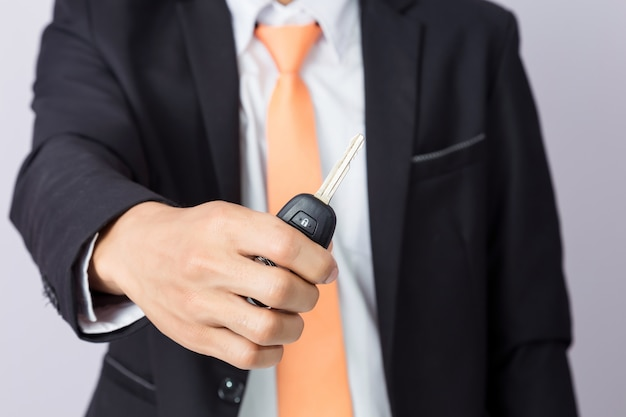 Businessman holding the  car key, isolated background