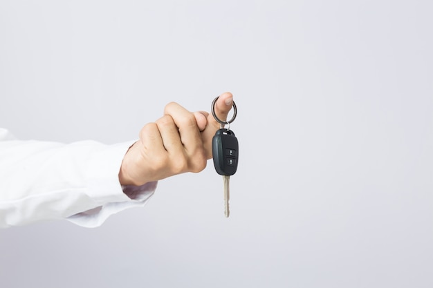 Businessman holding the  car key, isolated