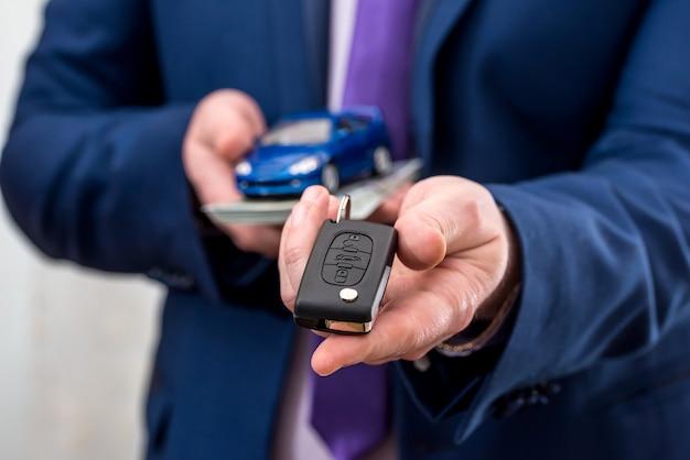 車のキー、おもちゃの車とお金を保持しているビジネスマン
