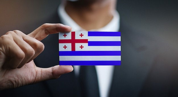 Businessman holding card of adjara flag