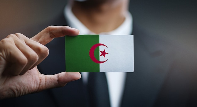Businessman holding card of algeria flag