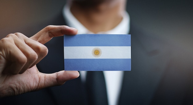 Businessman holding card of argentina flag