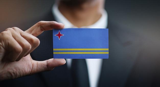 Businessman holding card of aruba flag